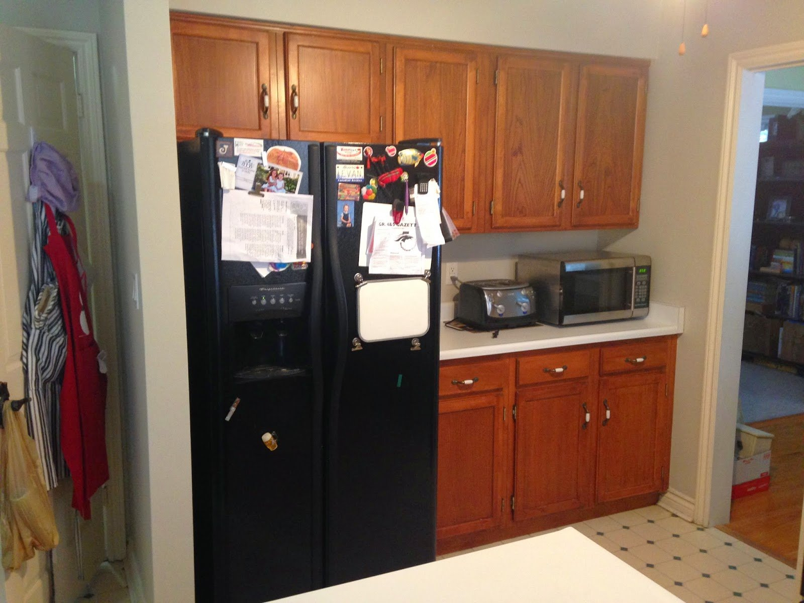Black fridge and old cupboards.